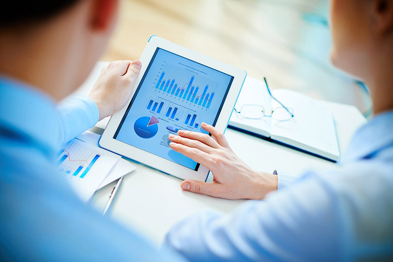 A professional with a tablet checking bar chart