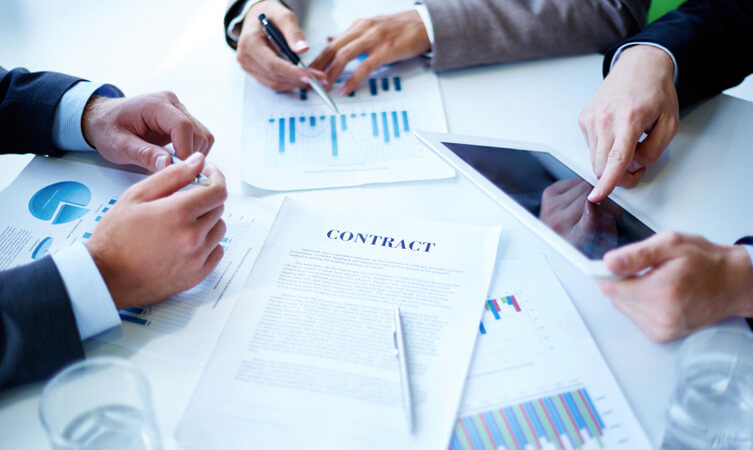 Professionals with a contract sheet checking tablet and bar charts