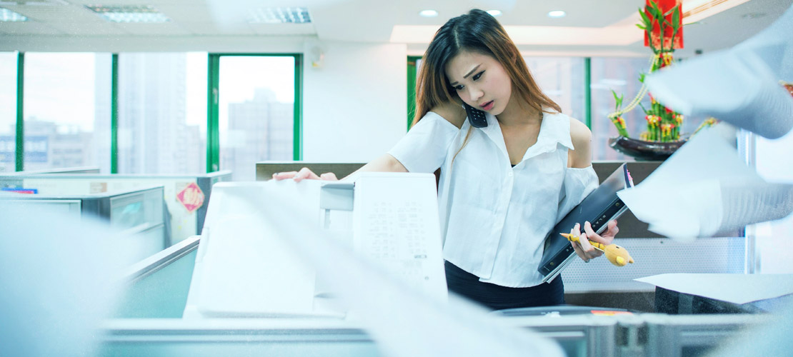 Chinese lady opening copier machine while on the phone