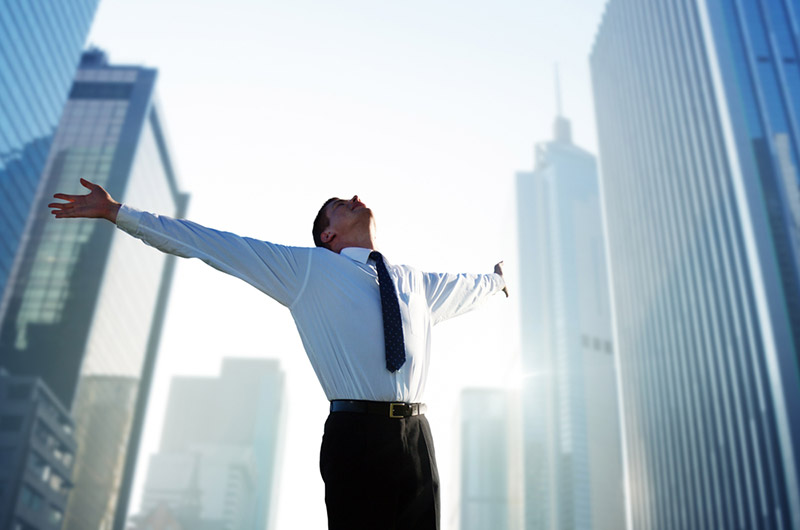 Man stretching arms looks over the sky